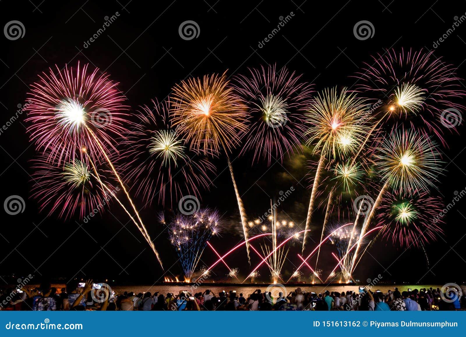 Веселя толпа наблюдая красочные фейерверки и празднуя на пляже во время фестиваля