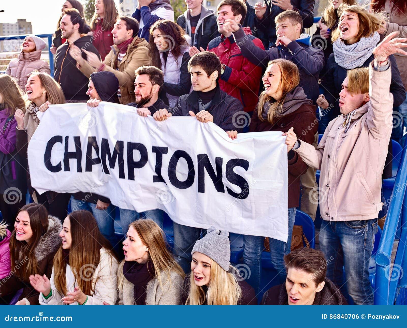 Веселя вентиляторы в стадионе держа знамя чемпиона