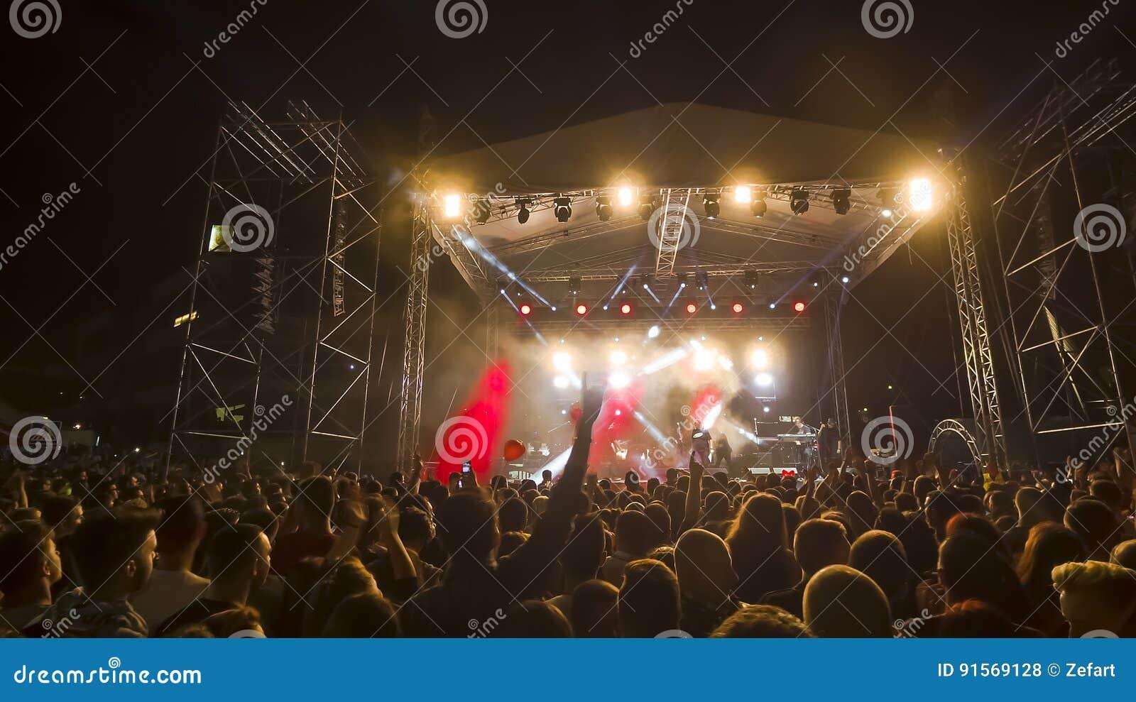 Веселя толпа перед яркими красочными светами этапа