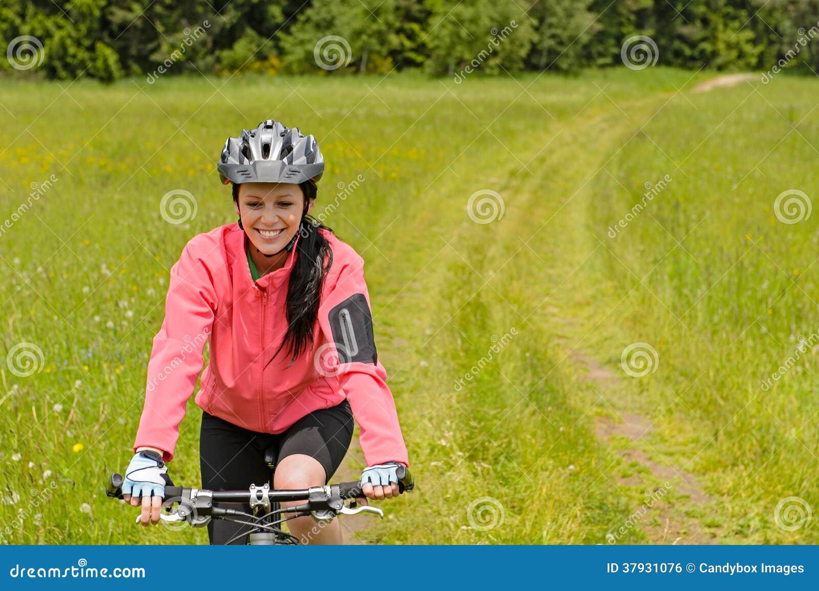 Велосипед катания женщины на пути луга