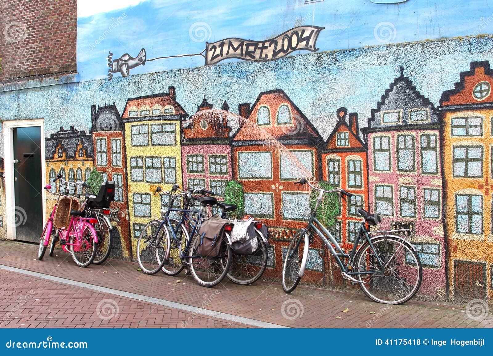 Велосипеды против стены граффити искусства улицы, Leeuwarden, Голландии