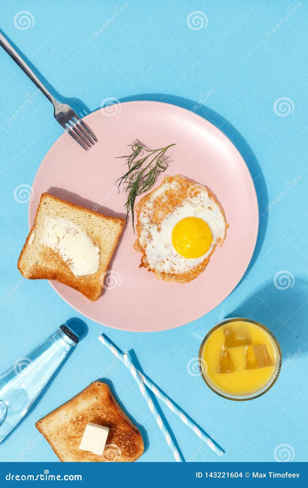 Взбитые яйца, умасленные тосты и напитки на голубой таблице Взгляд сверху завтрака