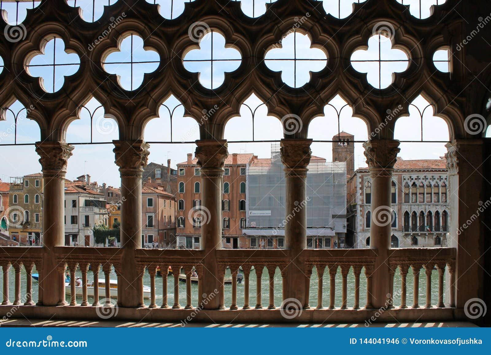 Взгляд большого канала Венеции через высекаенную белую каменную решетку дворца