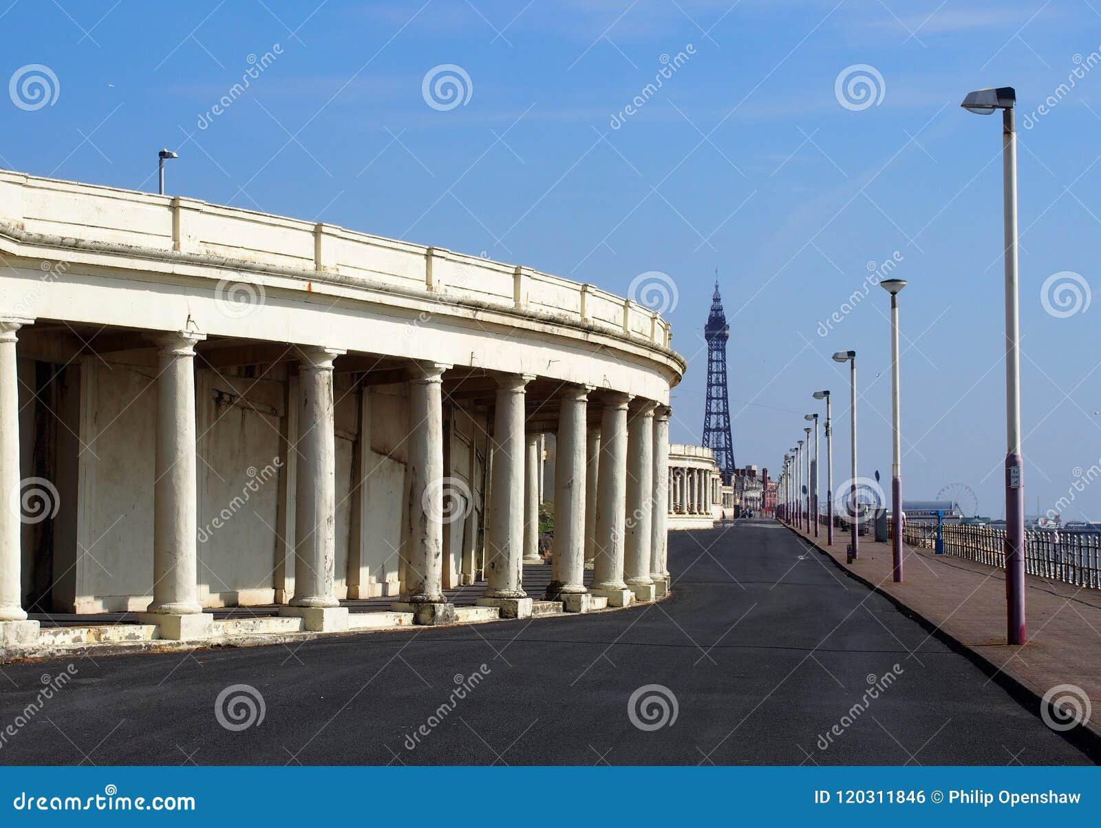 Взгляд вдоль прогулки на Блэкпуле показывая пешеходную дорожку со старыми укрытиями набережной смотря к пляжу удовольствия