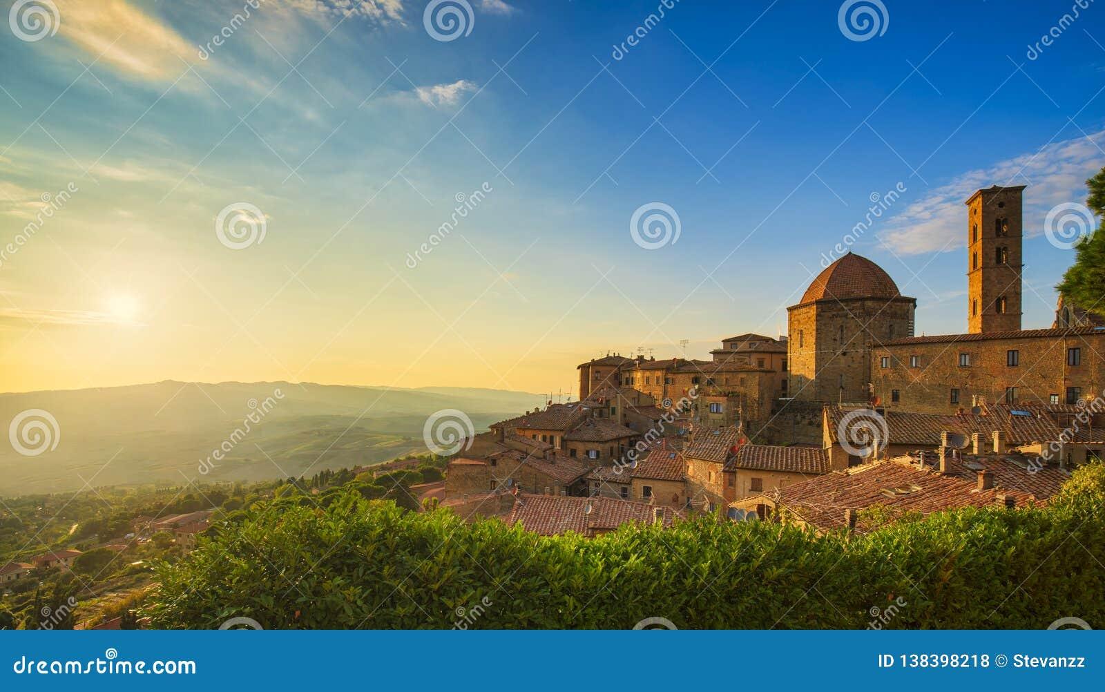 Взгляд горизонта городка Тосканы, Volterra, церков и панорамы на заходе солнца Италия