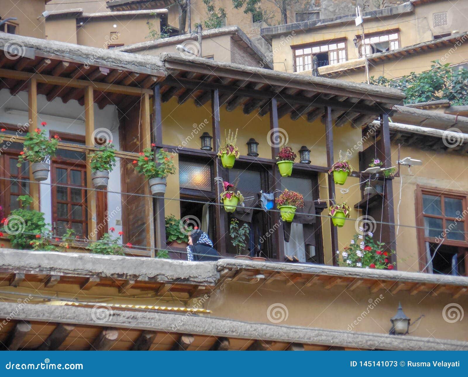 Взгляд деревянного дома в историческом городе Masouleh, цветках гераниума