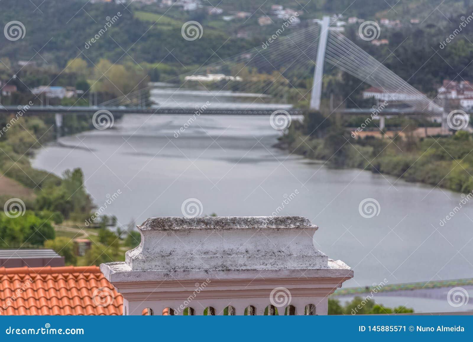 Взгляд детали традиционного камина, с запачканными рекой Mondego и мостом Rainha Santa Isabel как предпосылка в Коимбре, Португал