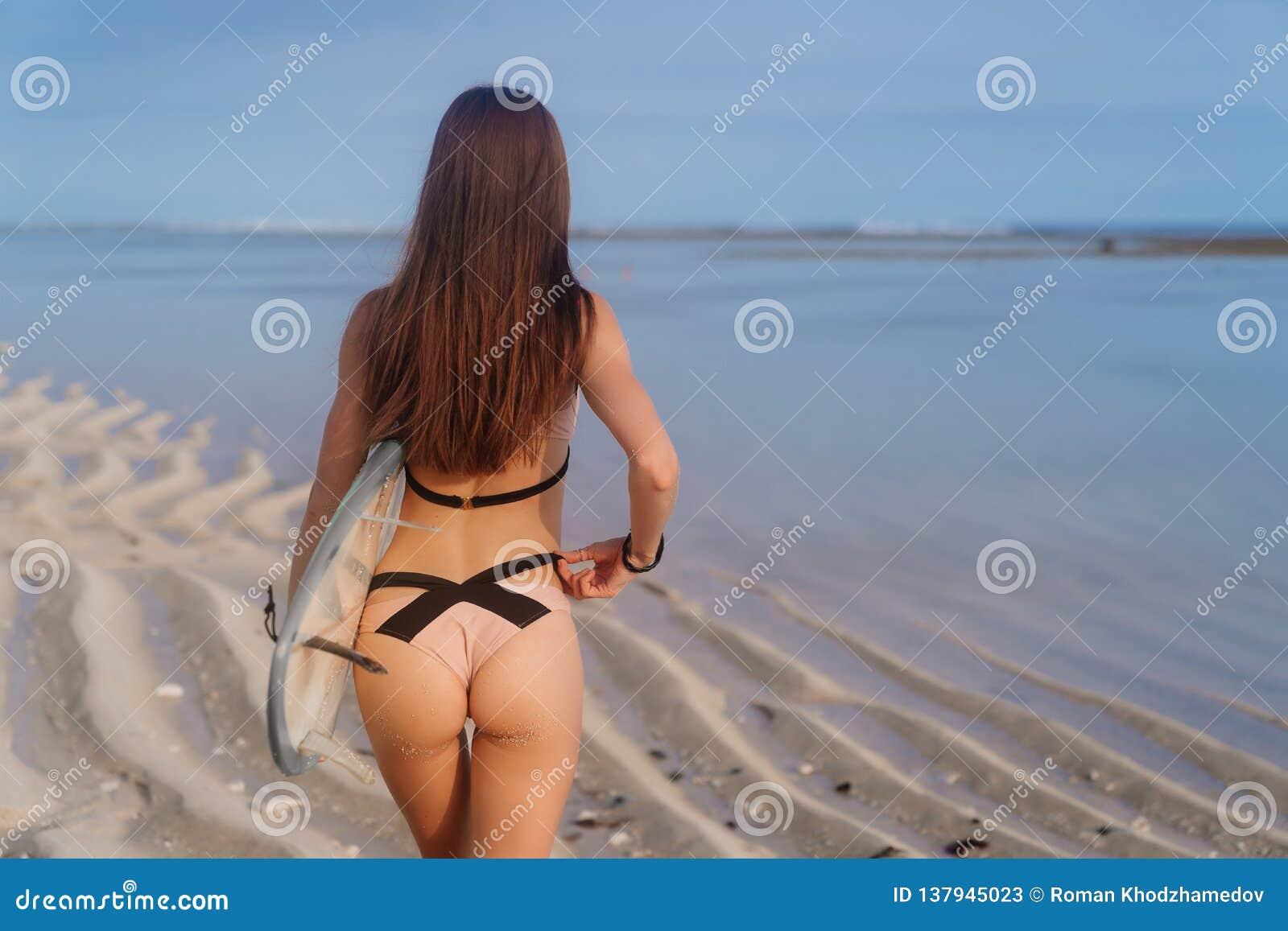 Взгляд задней стороны девушки с сексуальными батокс в купальнике и surfboard в ее руке на пляже