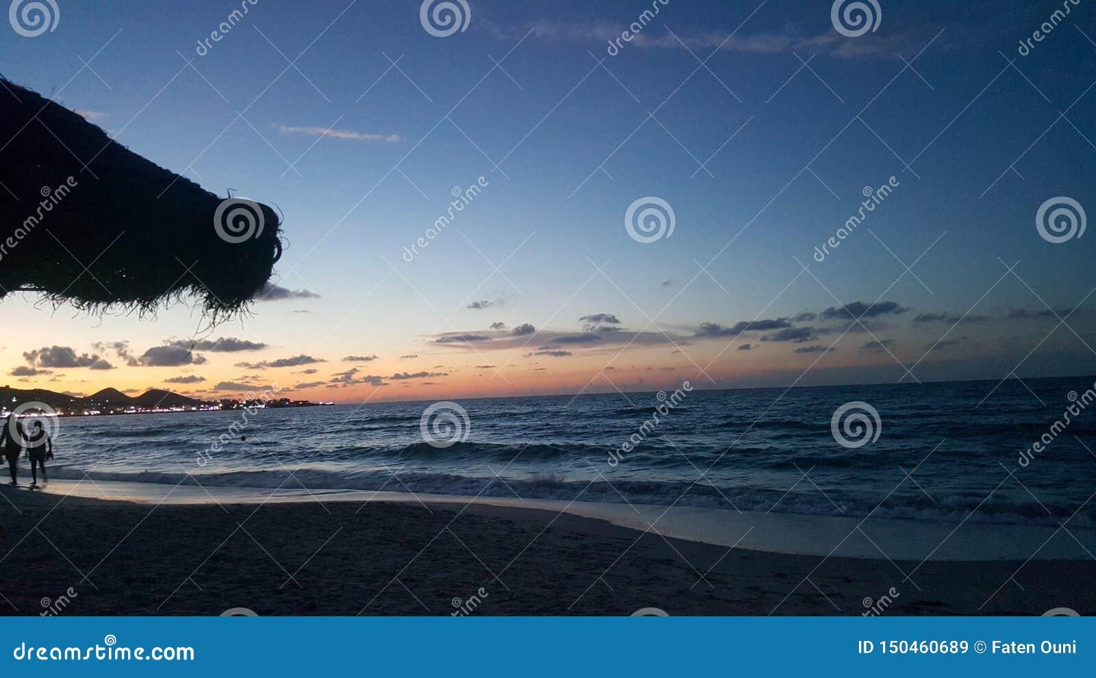 Взгляд захода солнца от пляжа