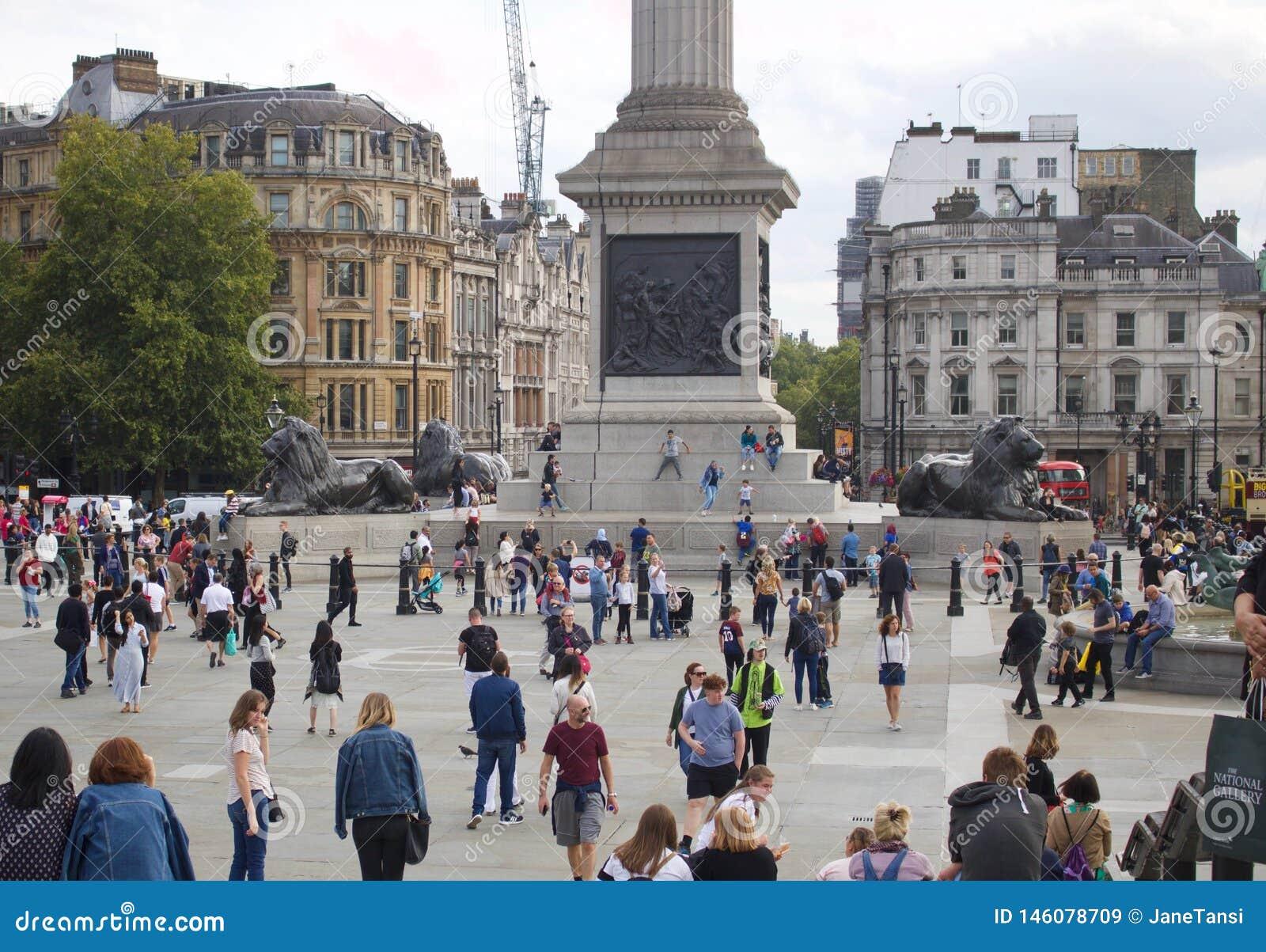 Взгляд квадрата Trafalgar Лондона с сериями людей идя о - изображении