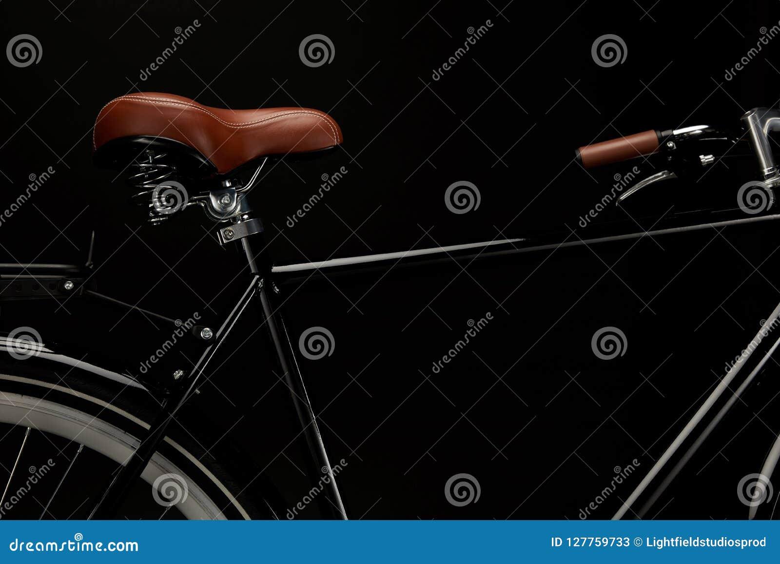 взгляд конца-вверх седловины и handlebar классического велосипеда изолированных на черноте