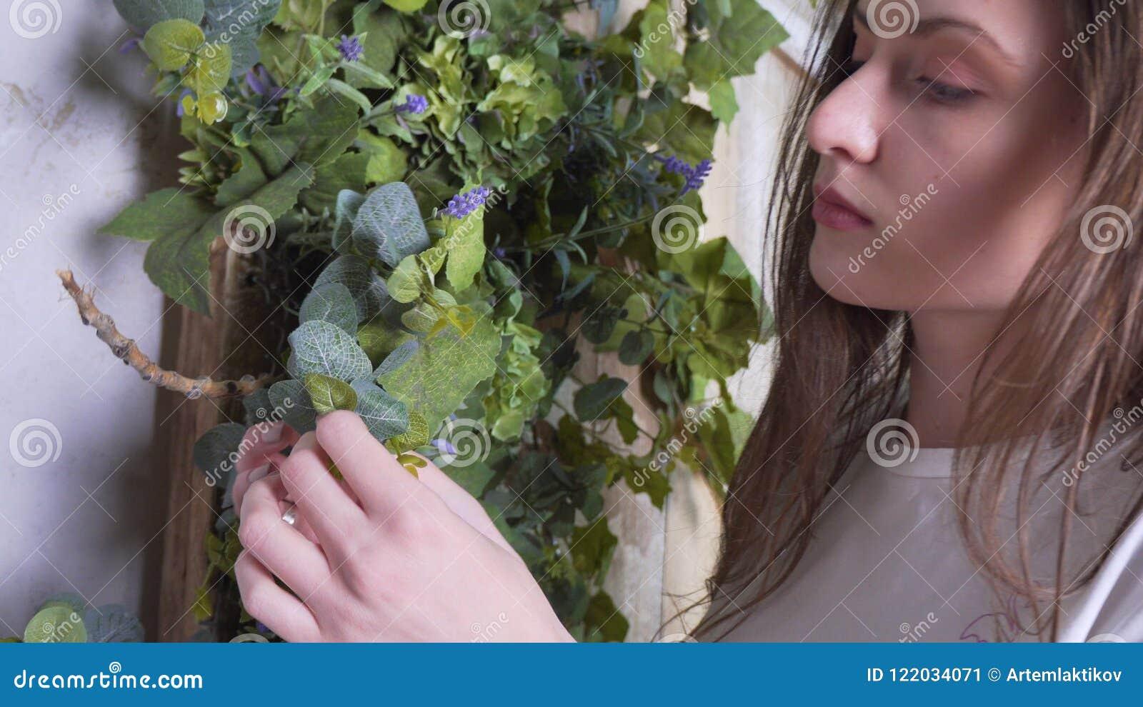 Взгляд конца-вверх, флорист женщины украшает красивое деревянное photozone с цветками