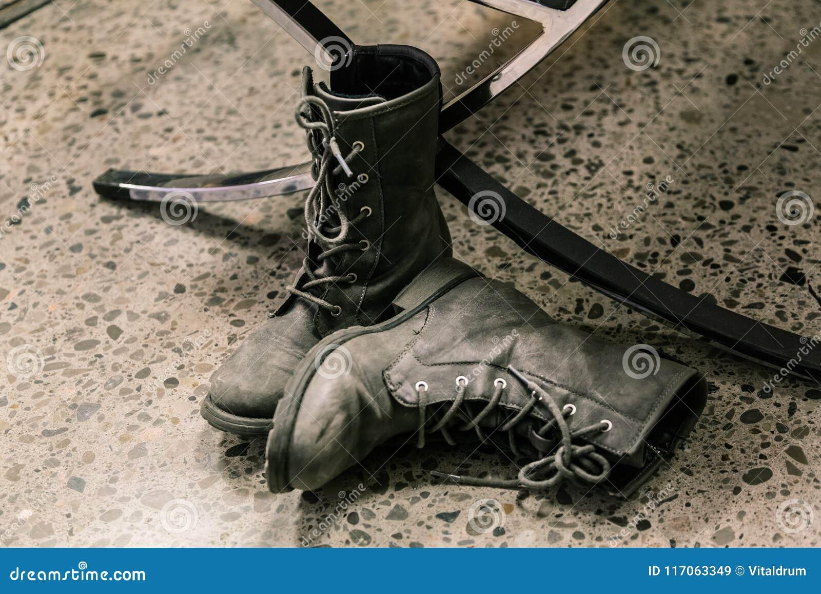 взгляд крупного плана темных серых пар стильных ботинок, носки ` s человека на темном конкретном поле