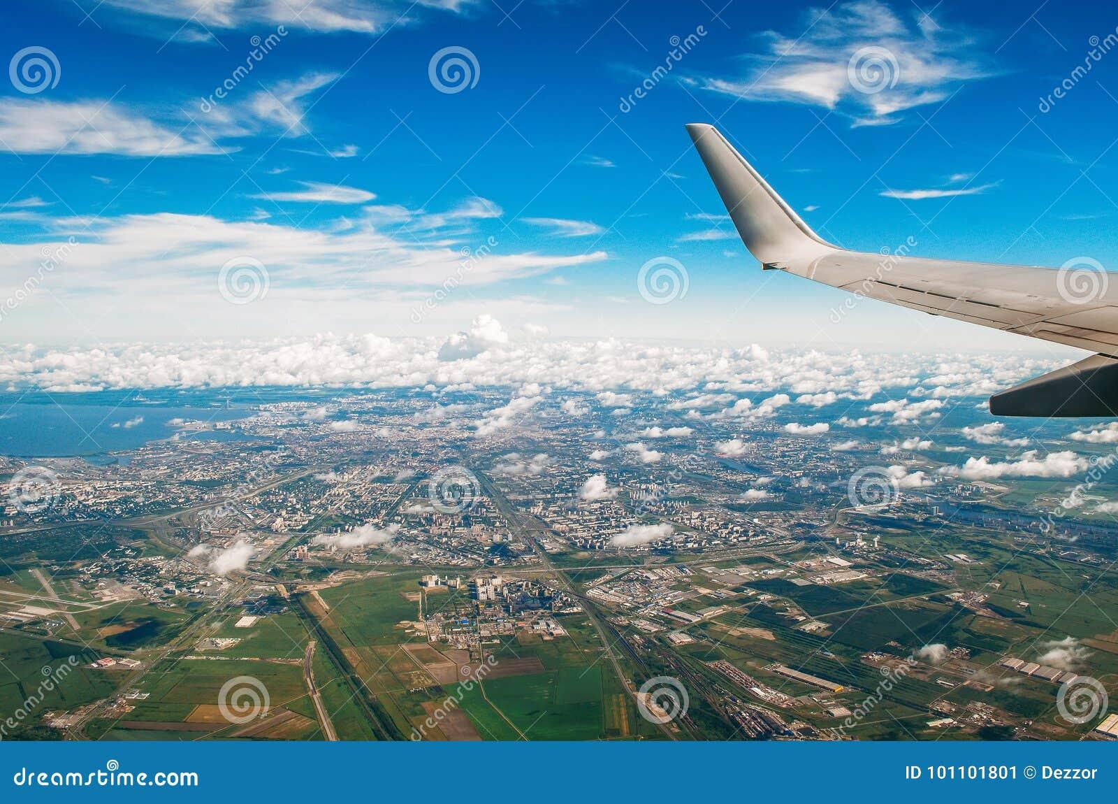 Взгляд крыла самолета в иллюминаторе на городе и авиапорте с живописными облаками