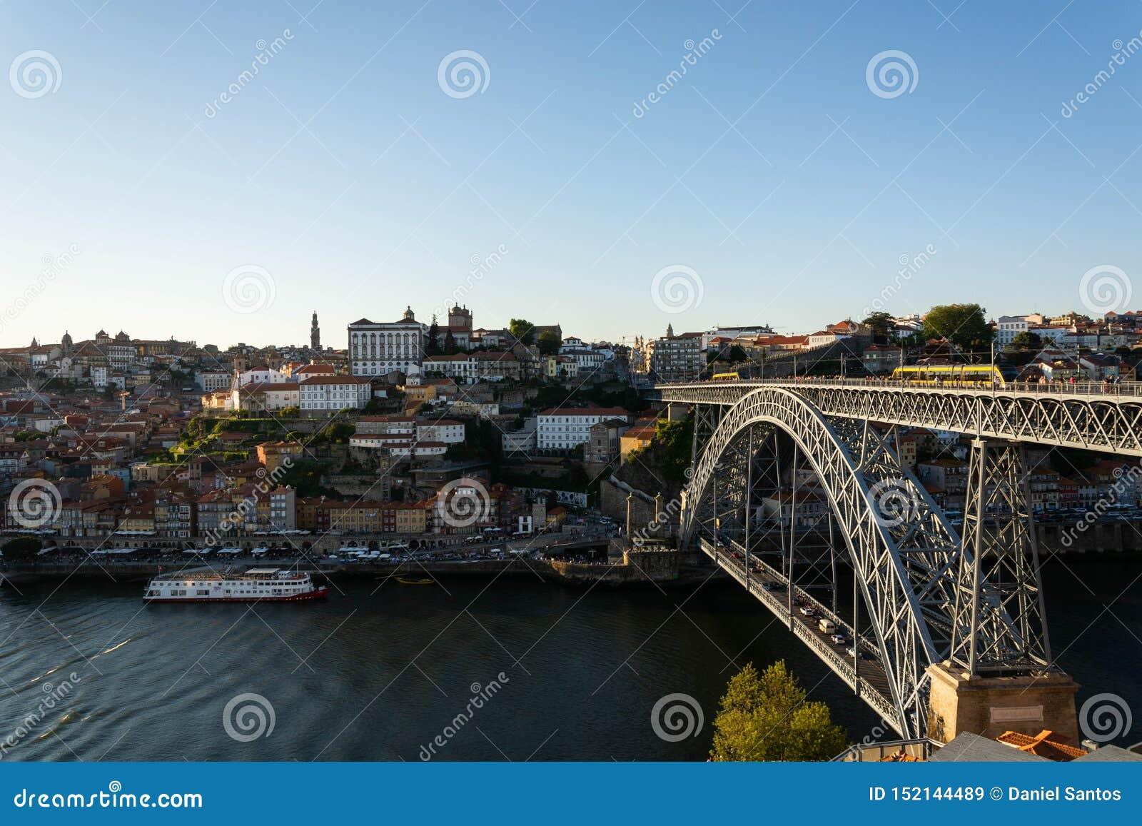 Взгляд к старому городу Порту с d Мост Луис и красочные здания Теплый золотой свет