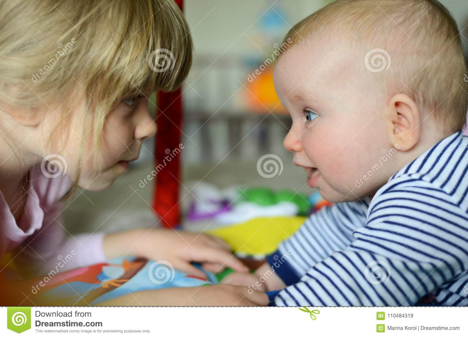 Взгляд 2 маленький прелестный кавказский сестер на одине другого Они счастлив и усмехаться