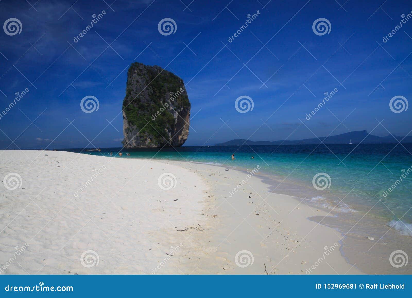 Взгляд над белым ярким пляжем песка на сиротливой известковой скале в темносинем море Andaman около Ao Nang, Krabi, Таиланда