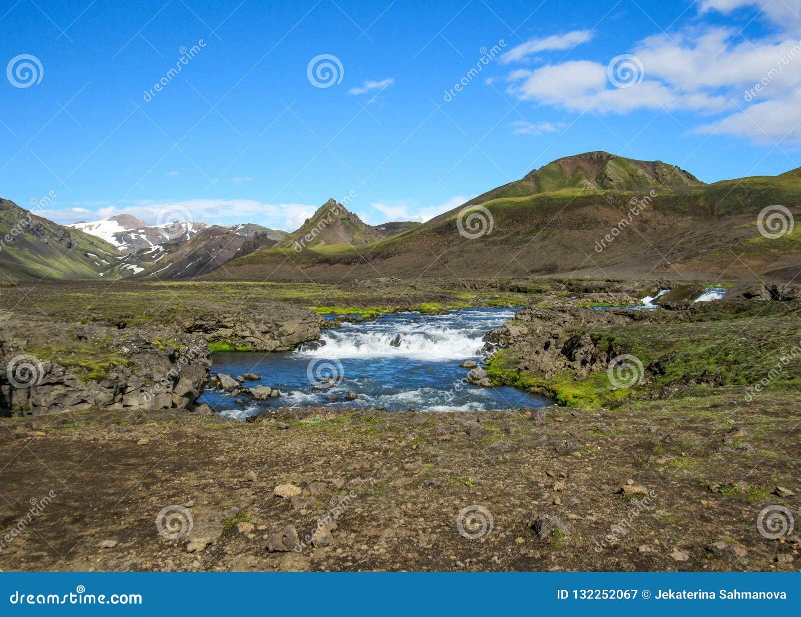 Взгляд на широком реке бежать от ледника окруженного сценарным ландшафтом, следа Myrdalsjokull Laugavegur, гористых местностей Ис