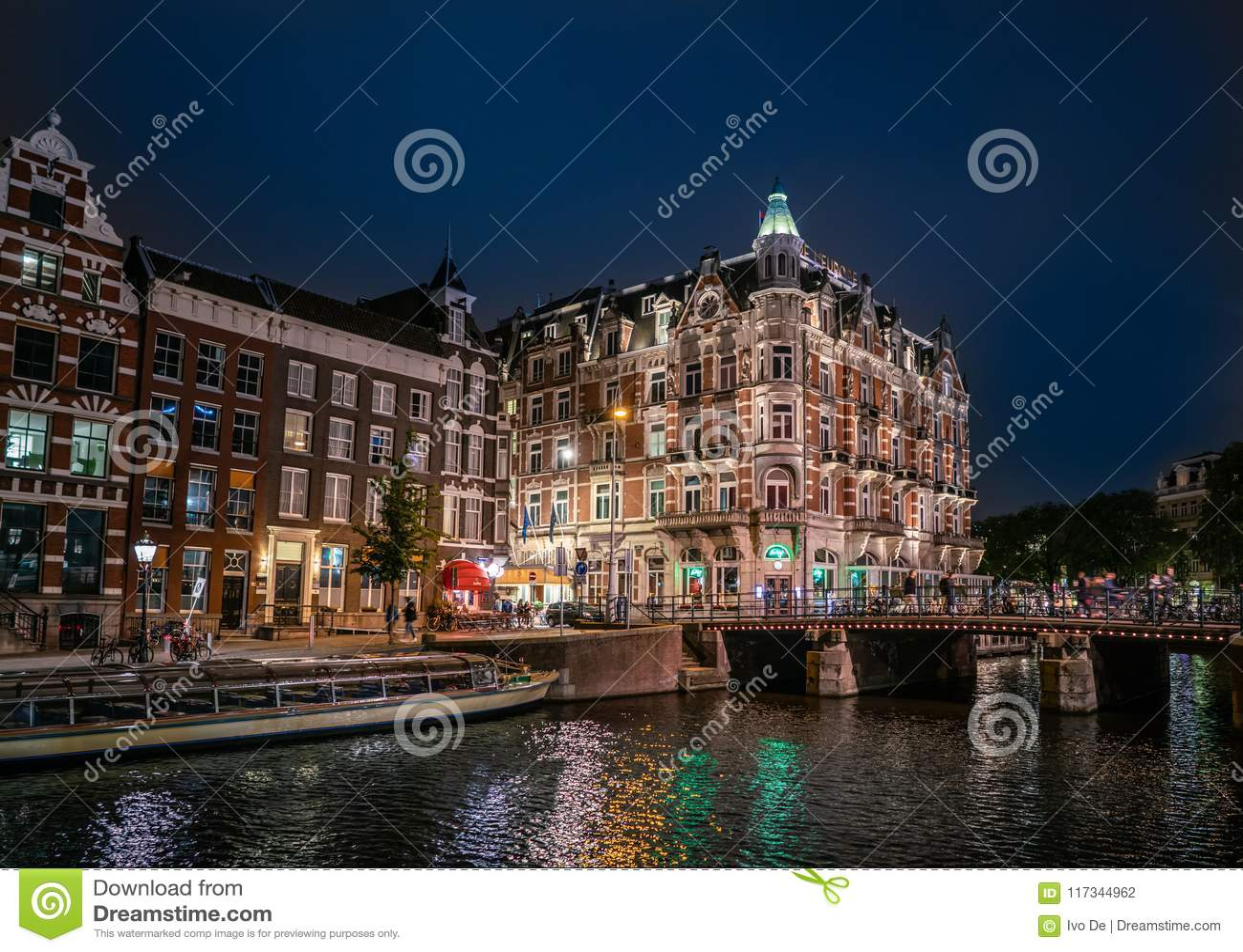 Взгляд ночи гостиницы l Европы 5 звезд на угле Rokin и реки Amstel