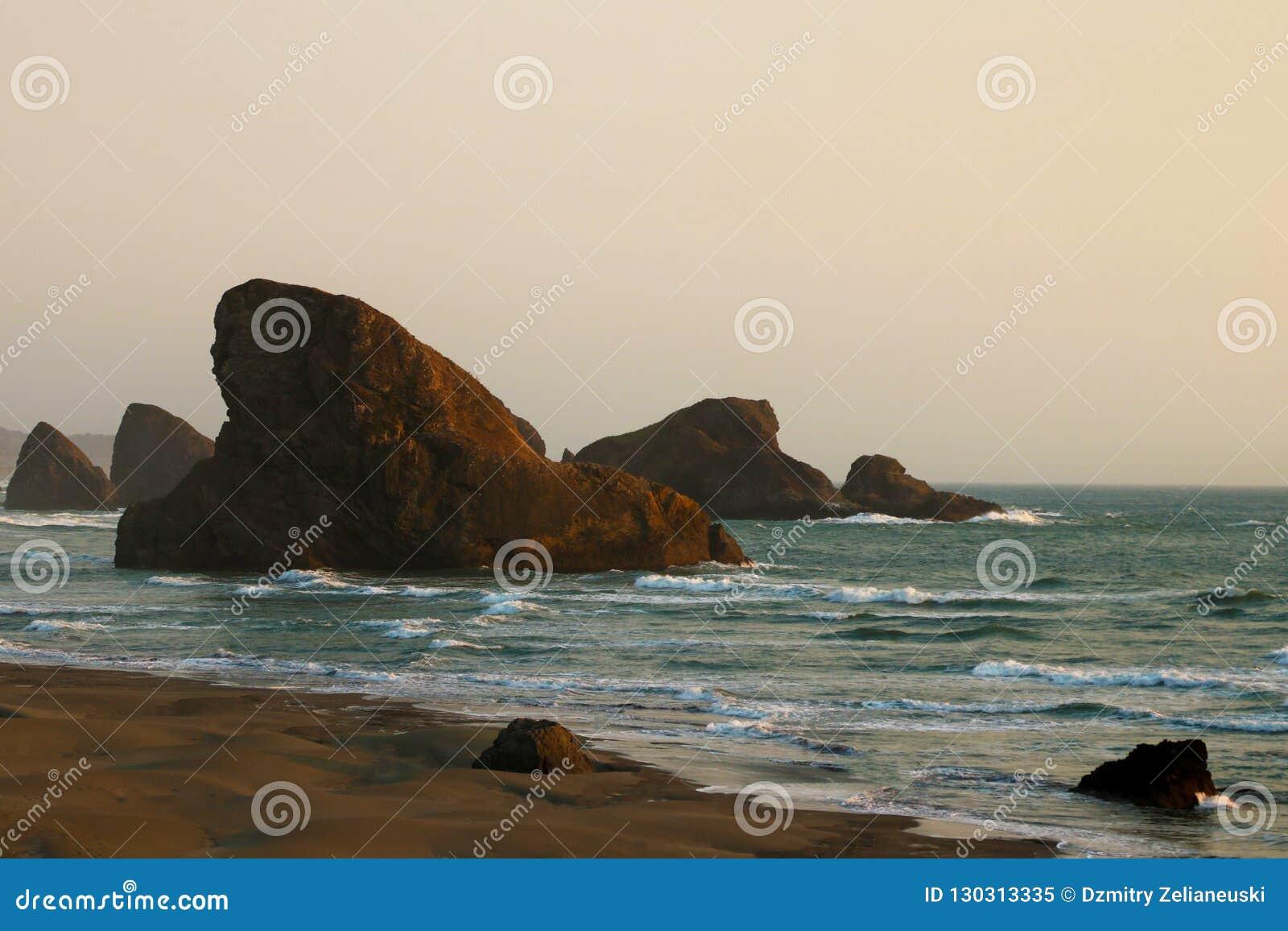 Взгляд океана на предпосылке красивого захода солнца подкрашивано