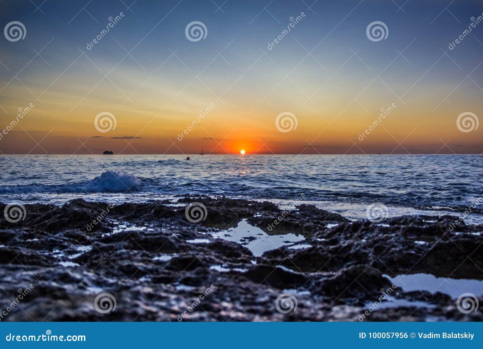 Взгляд от земли на восходе солнца в море