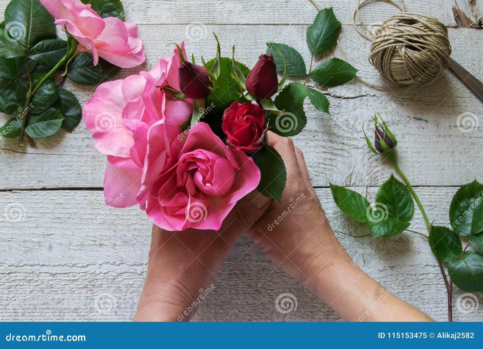 Взгляд сверху женского оформителя аранжируя розы на деревянном столе