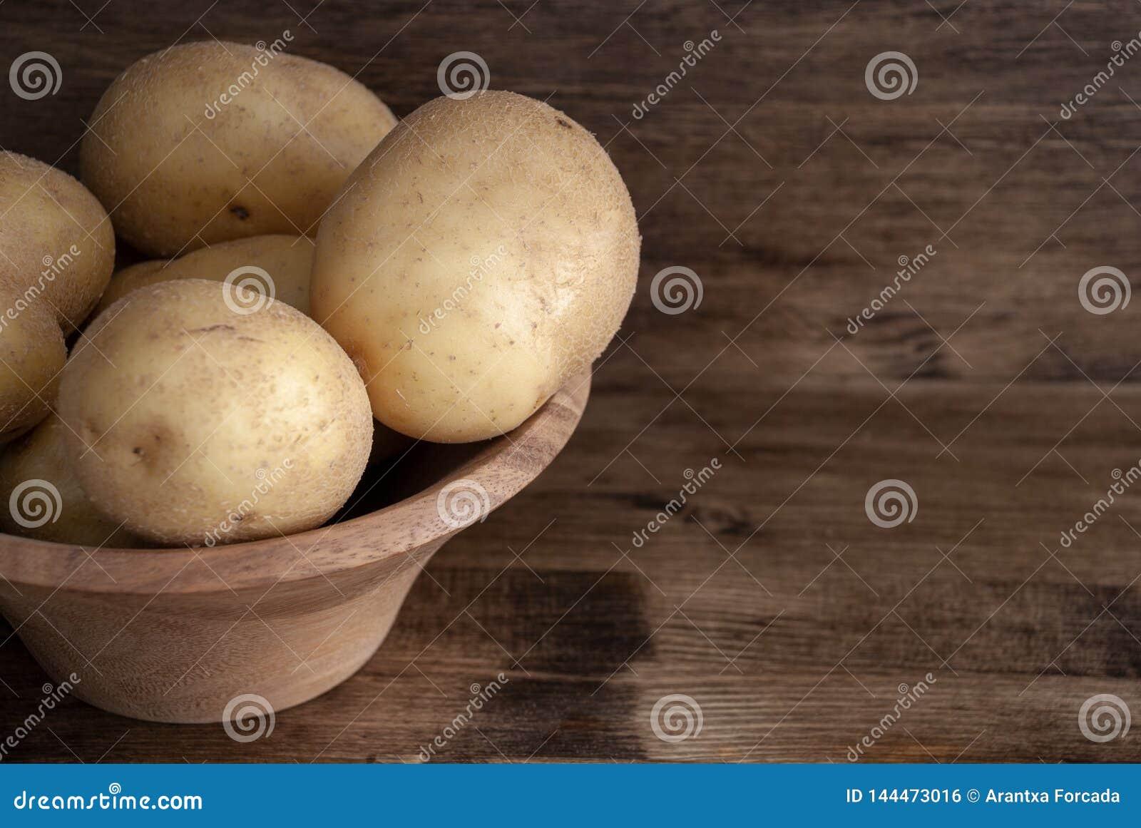 Взгляд сверху картошек в деревянном шаре