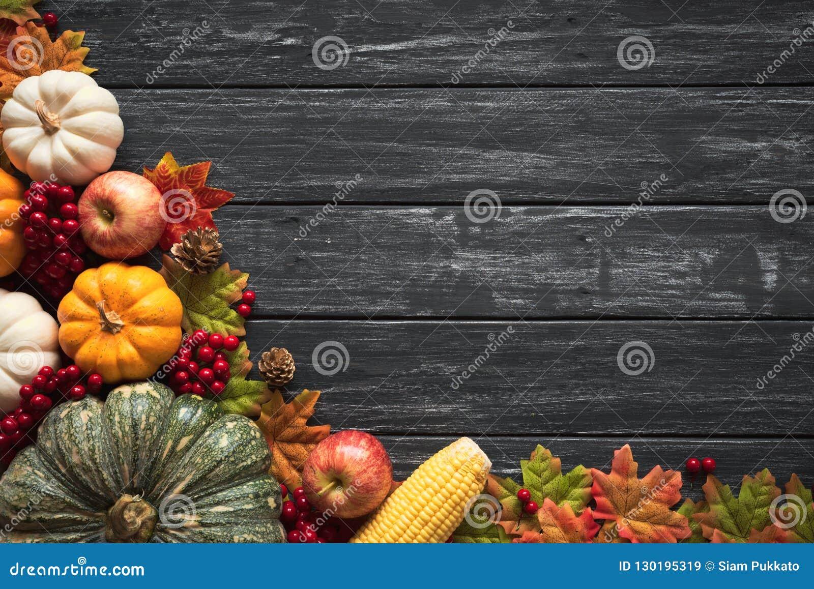 Взгляд сверху кленовых листов осени с тыквой и красными ягодами на старом деревянном backgound