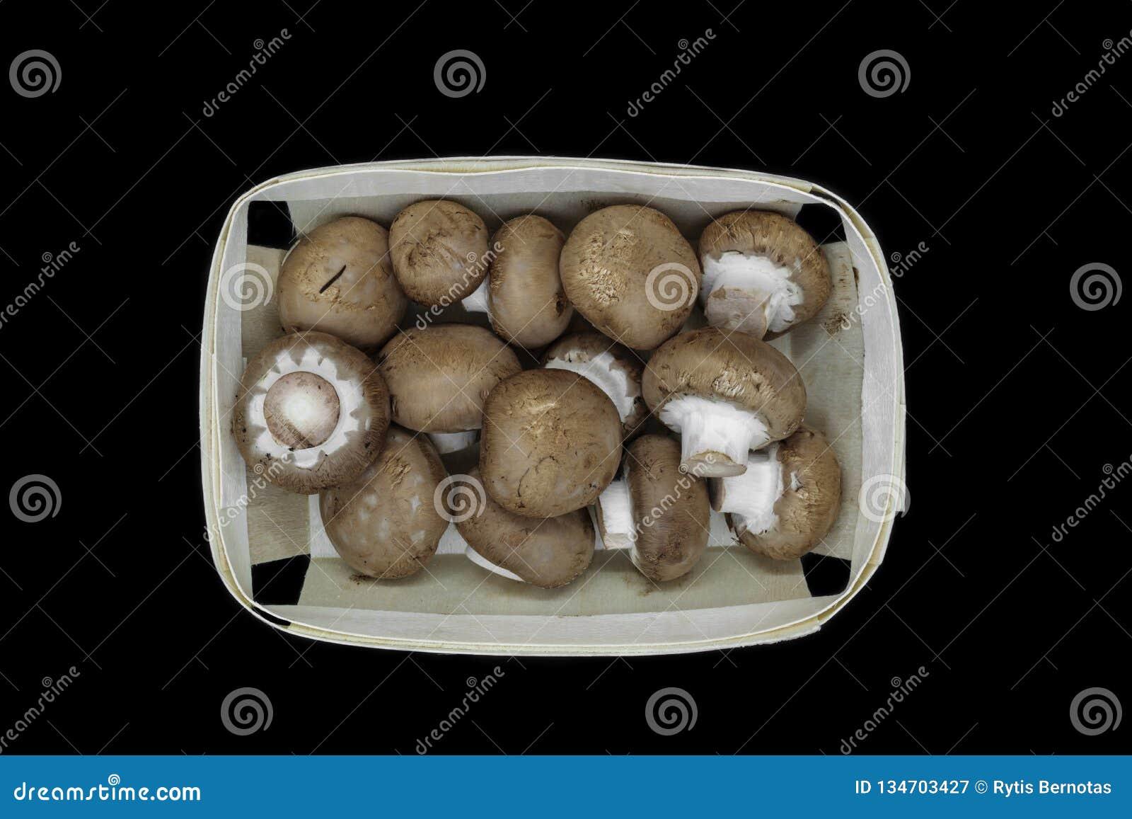 Взгляд сверху коричневых грибов champignons помещенных в деревянной корзине и изолированных на черной предпосылке