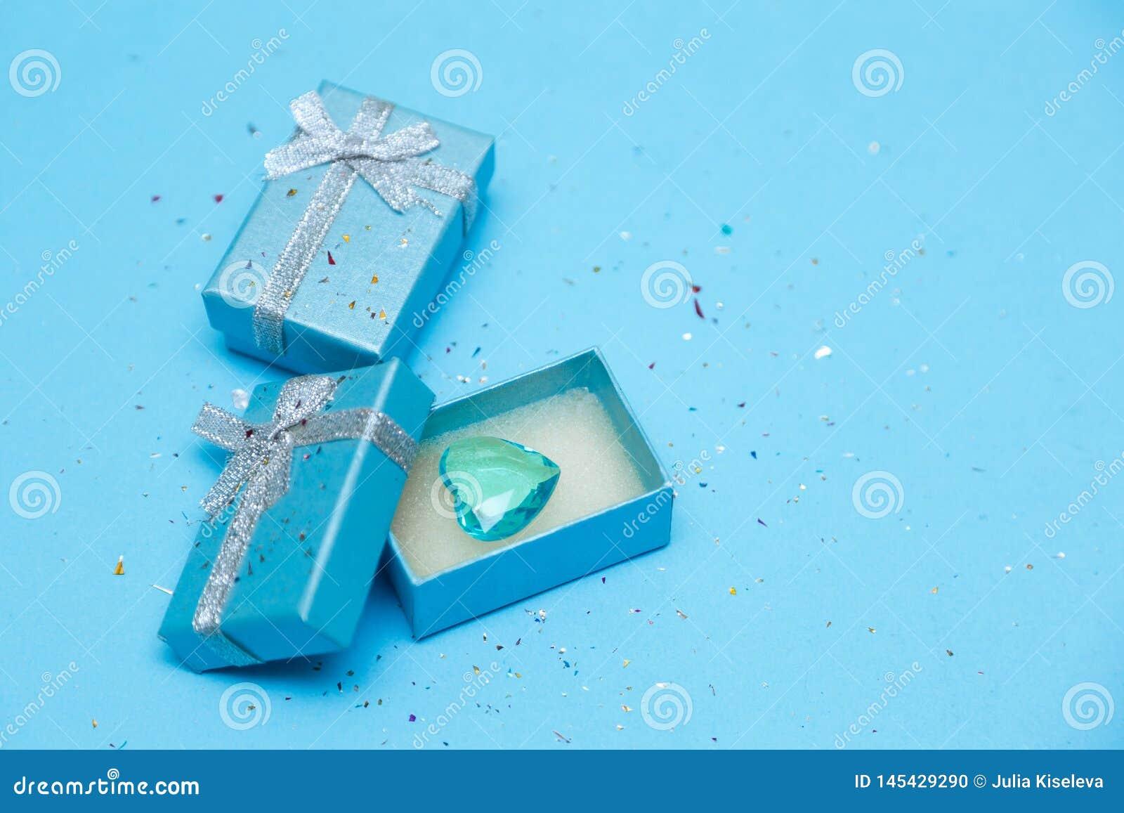 Взгляд сверху коробки связанной с лентой шелка на tiffany голубой предпосылке пастели цвета