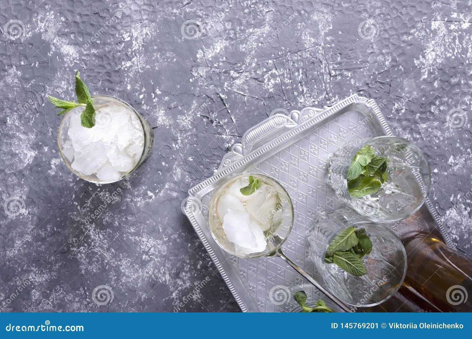 Взгляд сверху, который служат напитка julep мяты на винтажном серебряном подносе Стекла и мята в ей, задавленном льде и бутылках