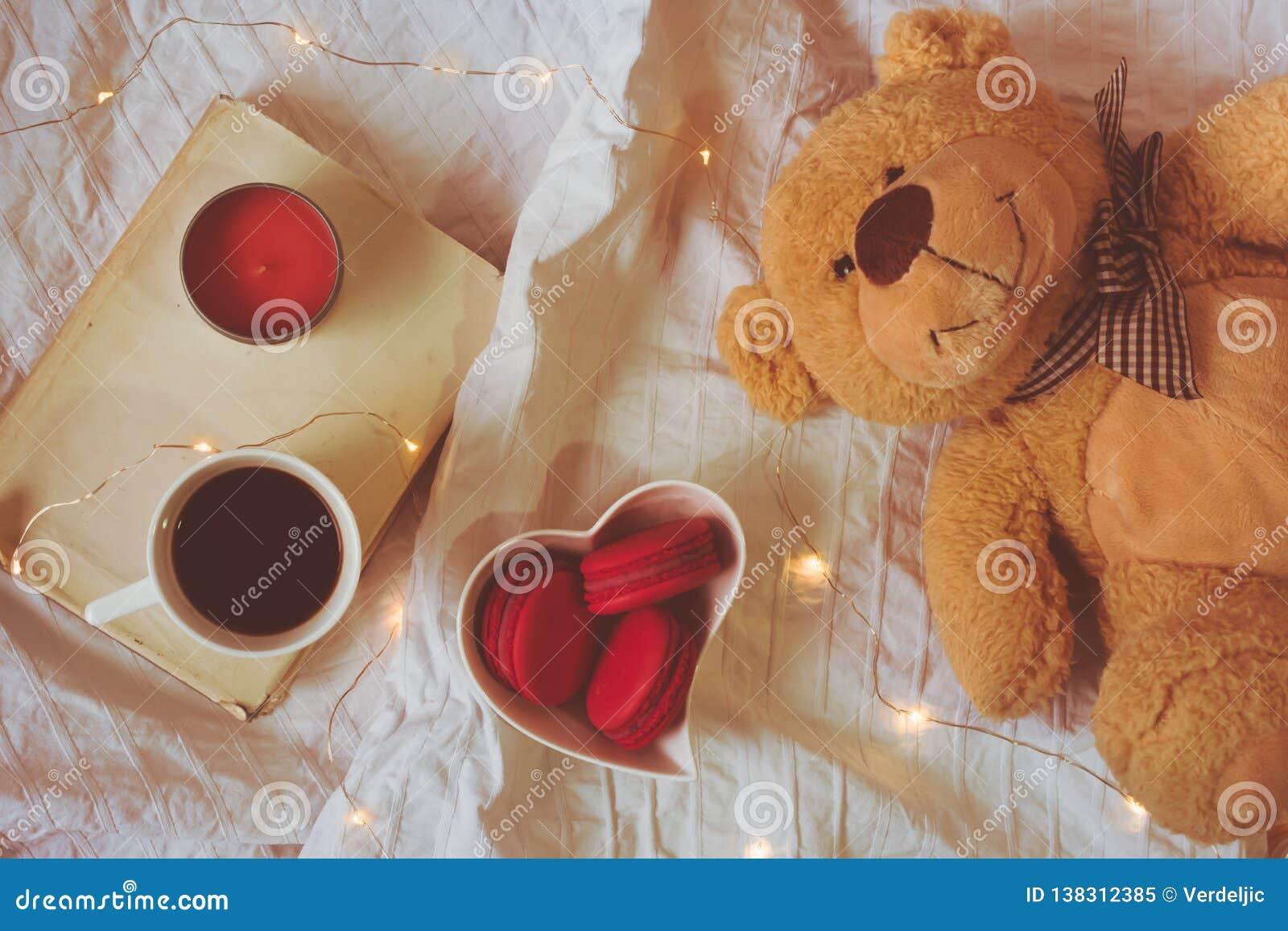 Взгляд сверху красных или розовых macarons в сердце сформировал шар, кофе, книгу, свечу и плюшевый мишку