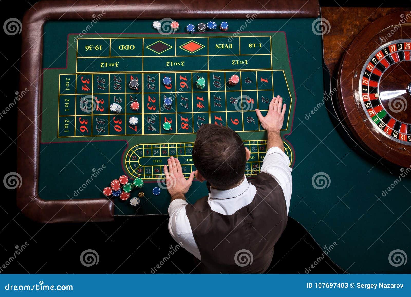 Взгляд сверху крупье казино и зеленой таблицы рулетки Ga