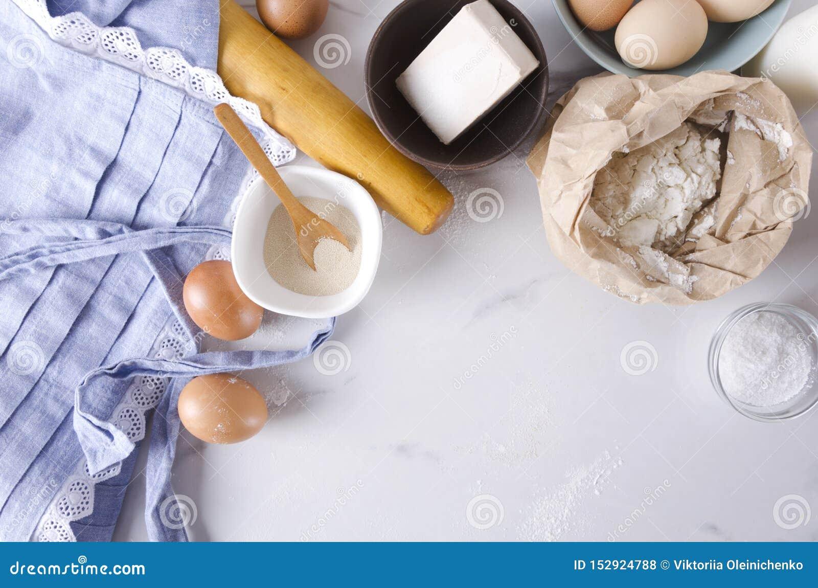 Взгляд сверху кухонного стола, ингредиентов для теста и делать товары пекарни, продукты Пустой космос для вашего текста