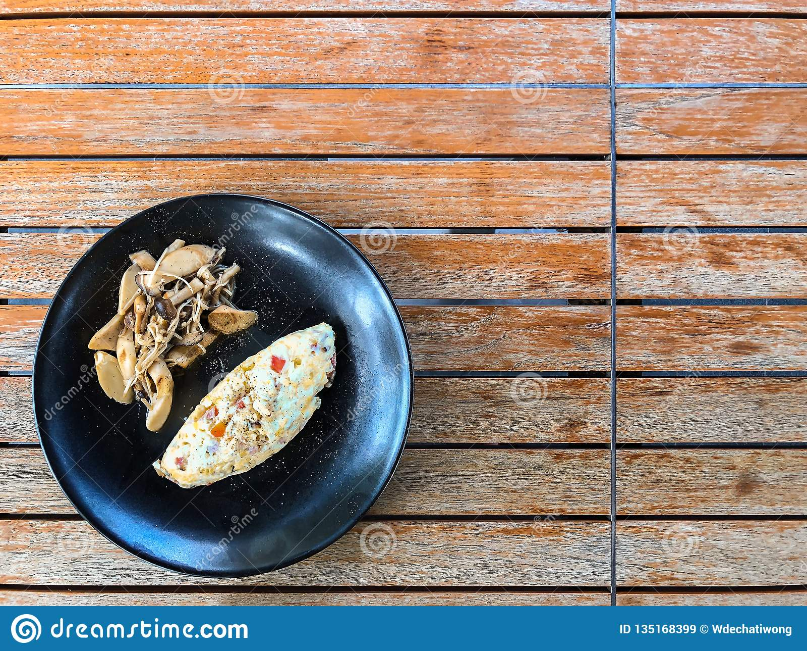 Взгляд сверху омлета здорового яйца белого с грибом orinji на черной плите и деревянном столе