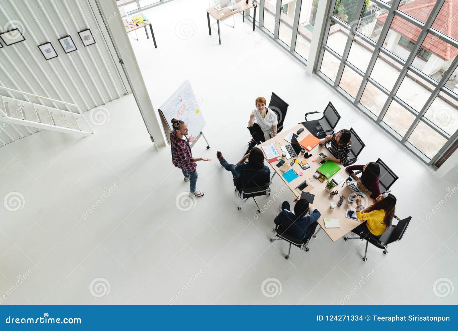 Взгляд сверху разнообразных людей творческой группы команды используя компьтер-книжку smartphone, мобильного телефона, таблетки и