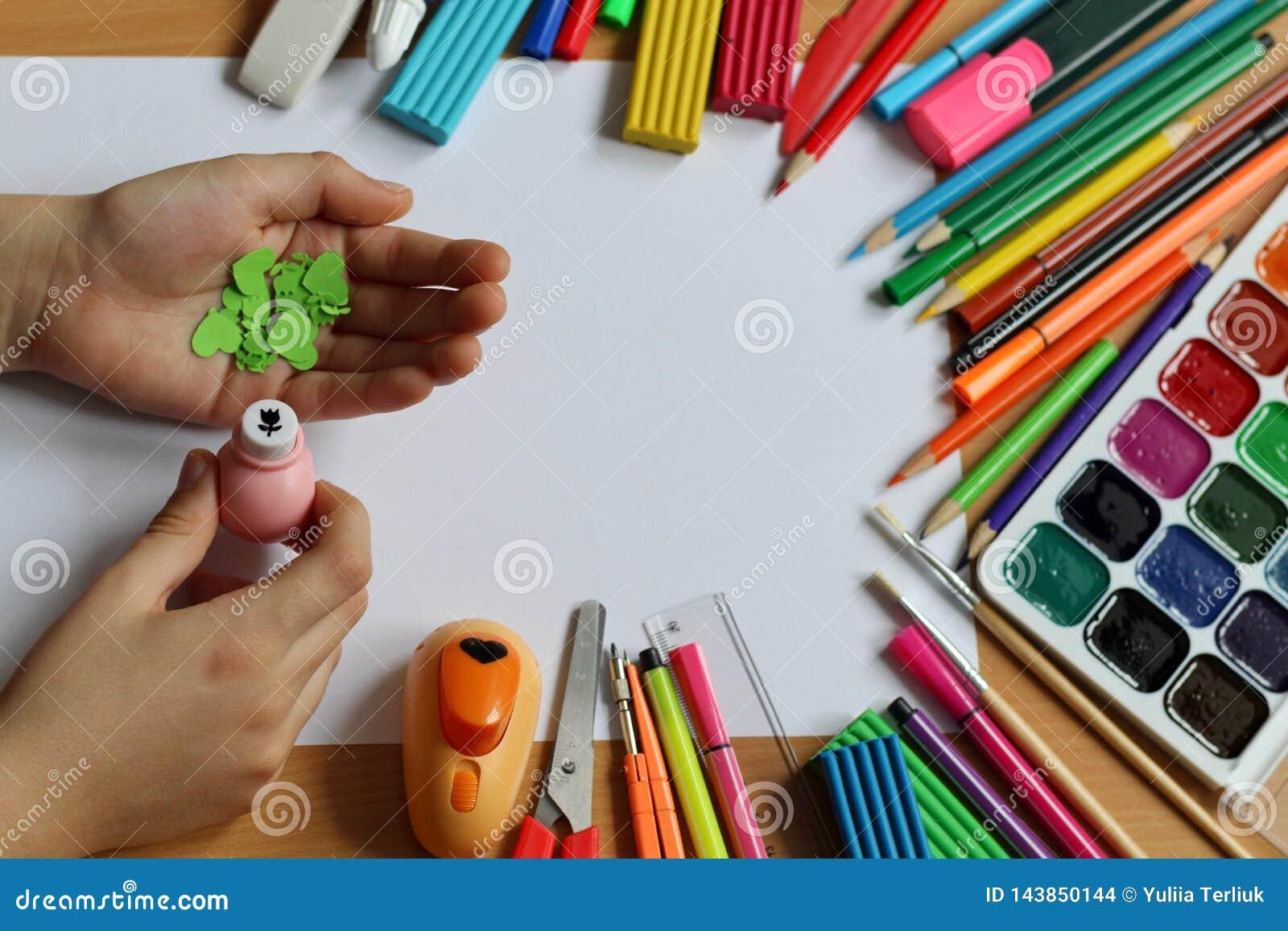 Взгляд сверху таблицы с чистым листом бумаги и руками младенца которые делают подарок День матери и день женщин Назад к schoo