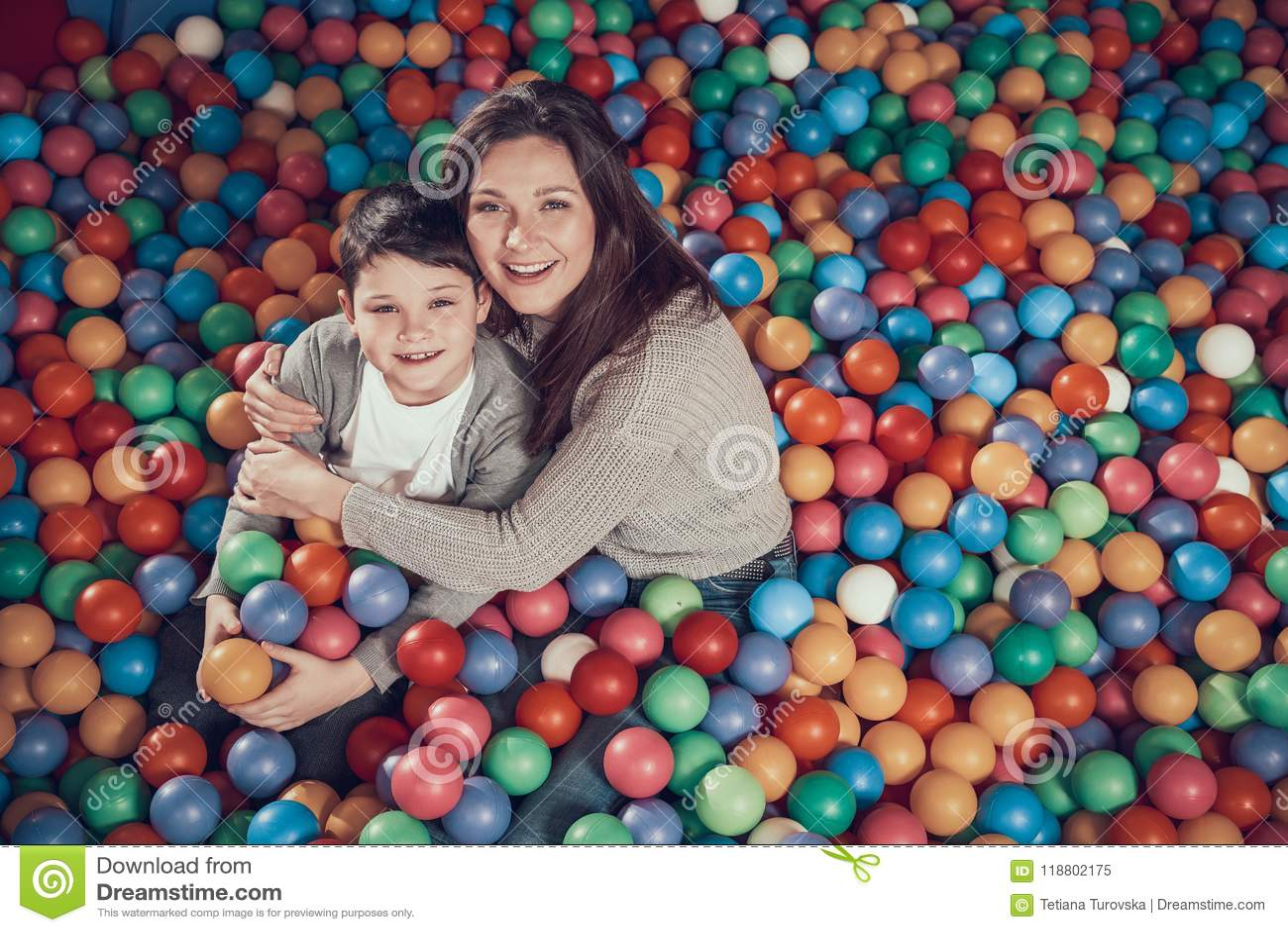 Взгляд сверху Усмехаясь мама и сын в бассейне с шариками