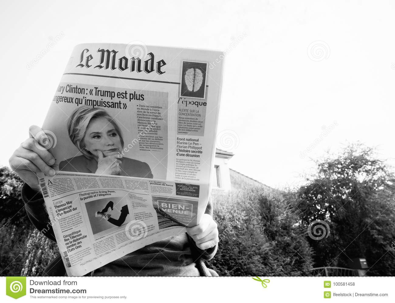 Взгляд снизу женщины читая самую последнюю газету Le Monde с портретом Хиллари Клинтон