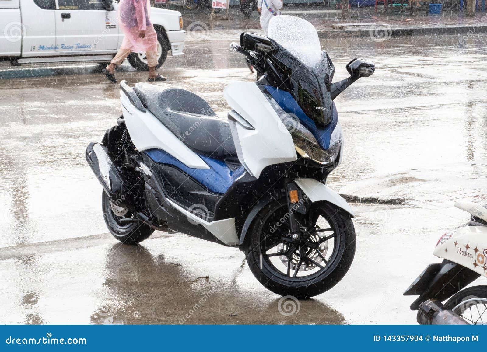 Взгляд со стороны бело-голубой стоянки 2018 мотоцикла Honda Forza 300 на бортовой прогулке в идти дождь день