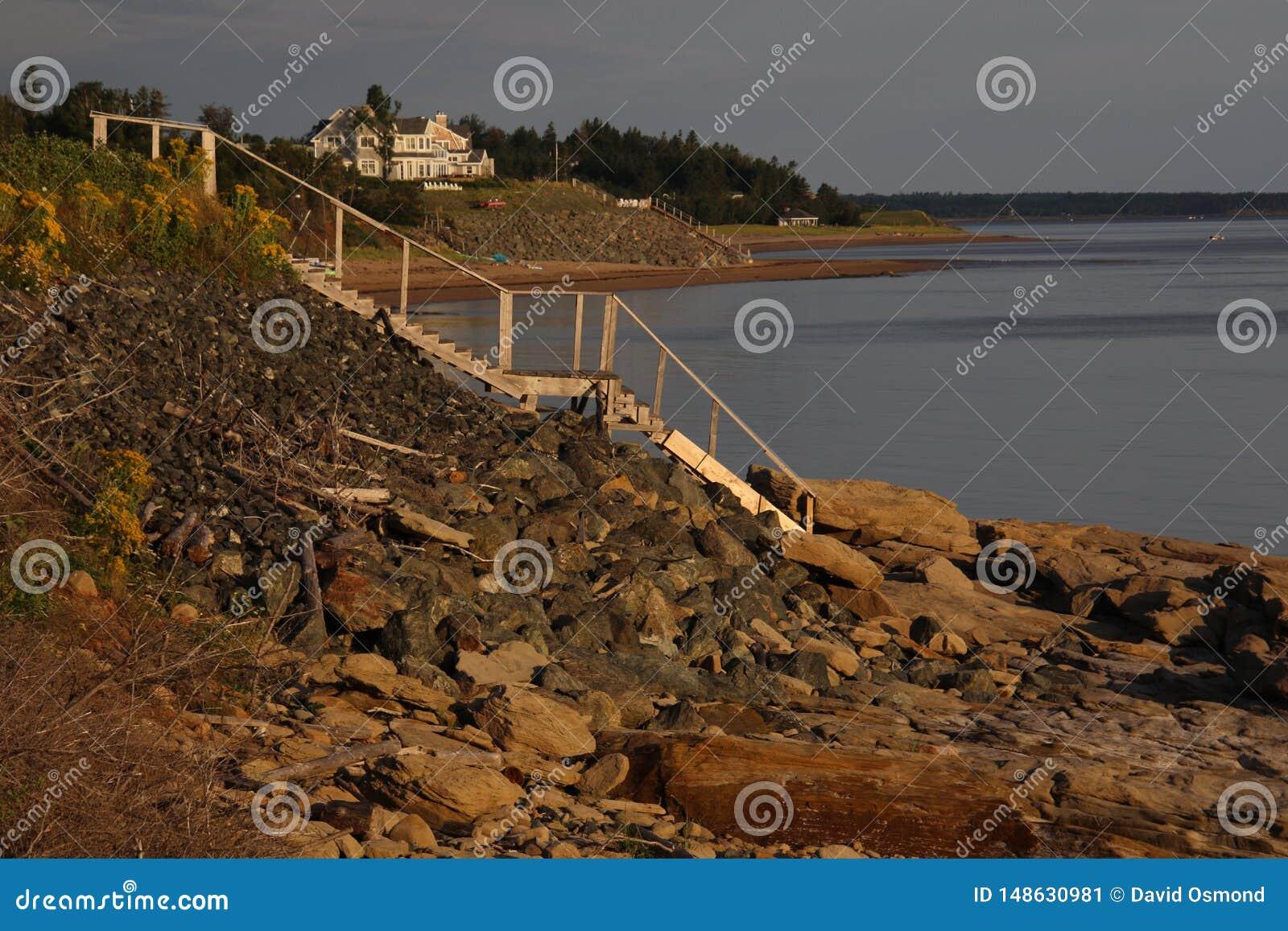Взгляд со стороны деревянной лестницы водя вниз к воде от холма