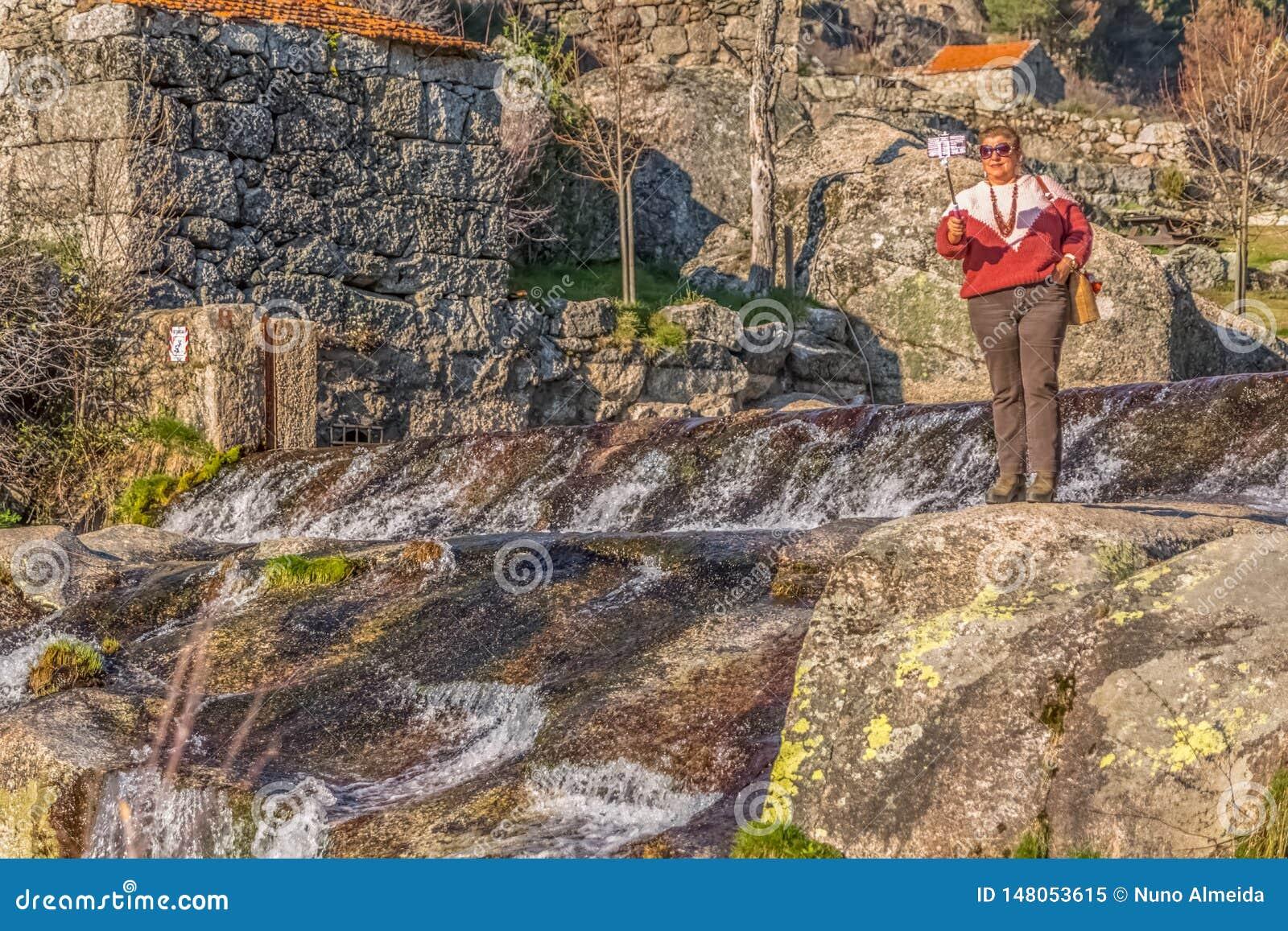 Взгляд старухи фотографируя с мобильным телефоном на ручке, около реки с большими granitic утесами