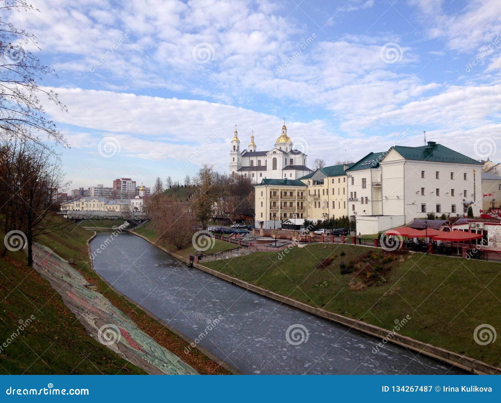 Взгляд церков и зданий за рекой, покрытый с льдом, против голубого неба с облаками Витебск, Беларусь