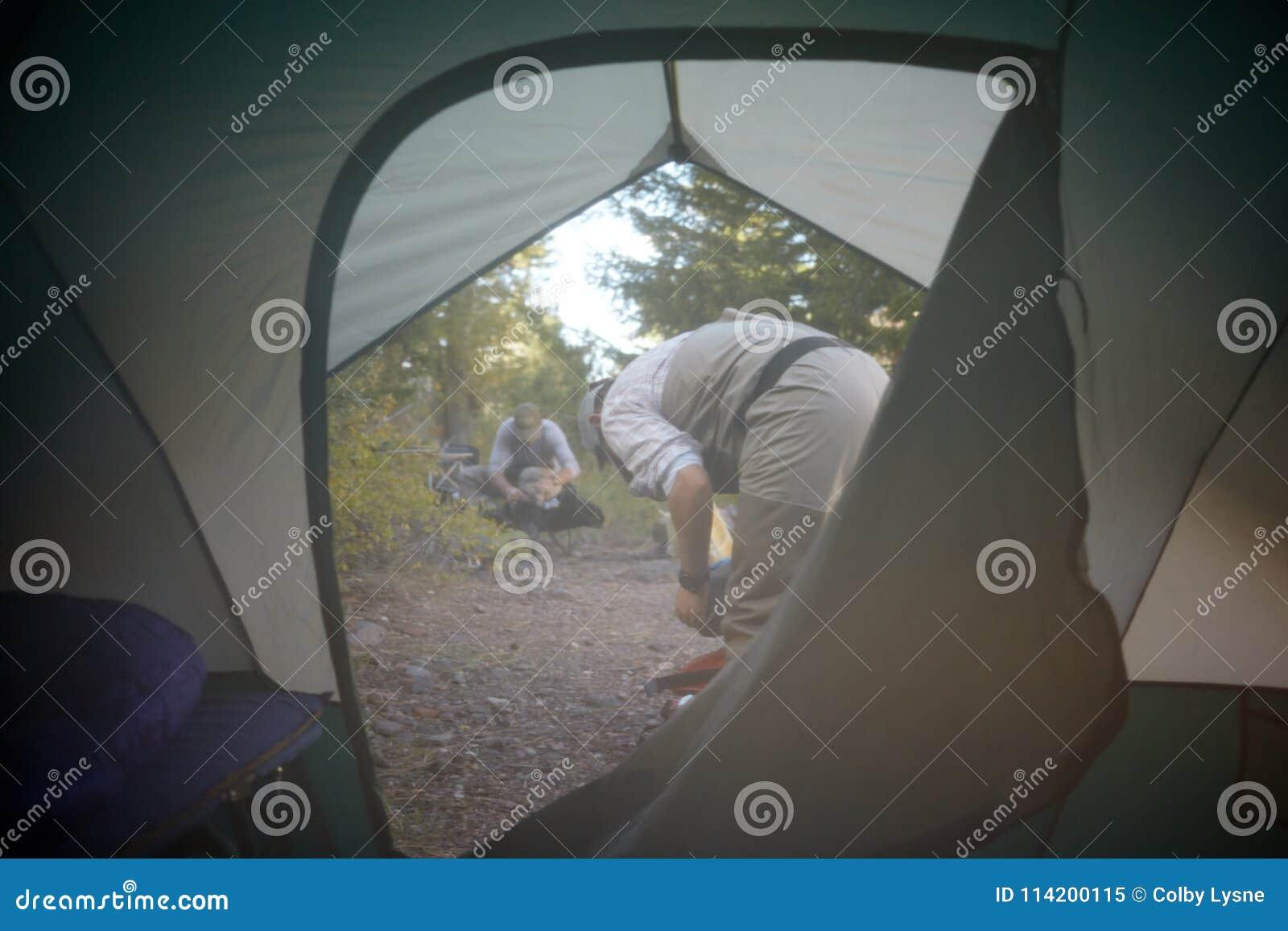 Взгляд через щиток шатра людей в месте для лагеря