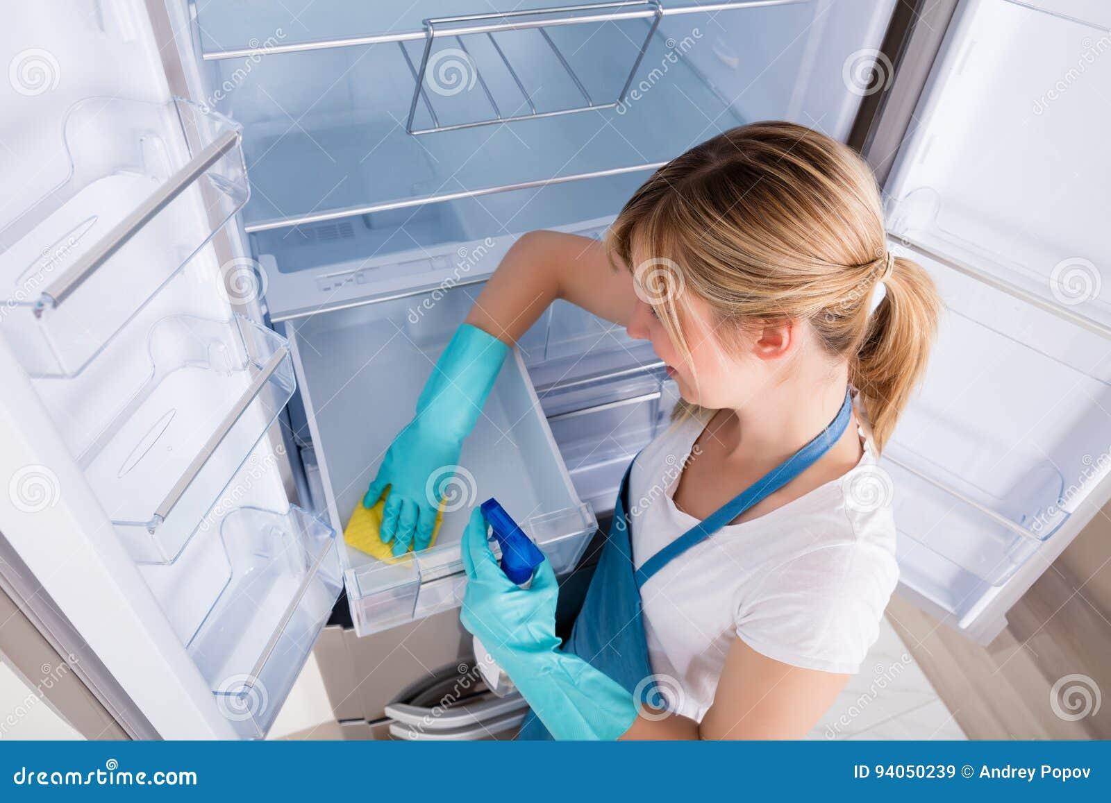 Взгляд высокого угла холодильника чистки женщины