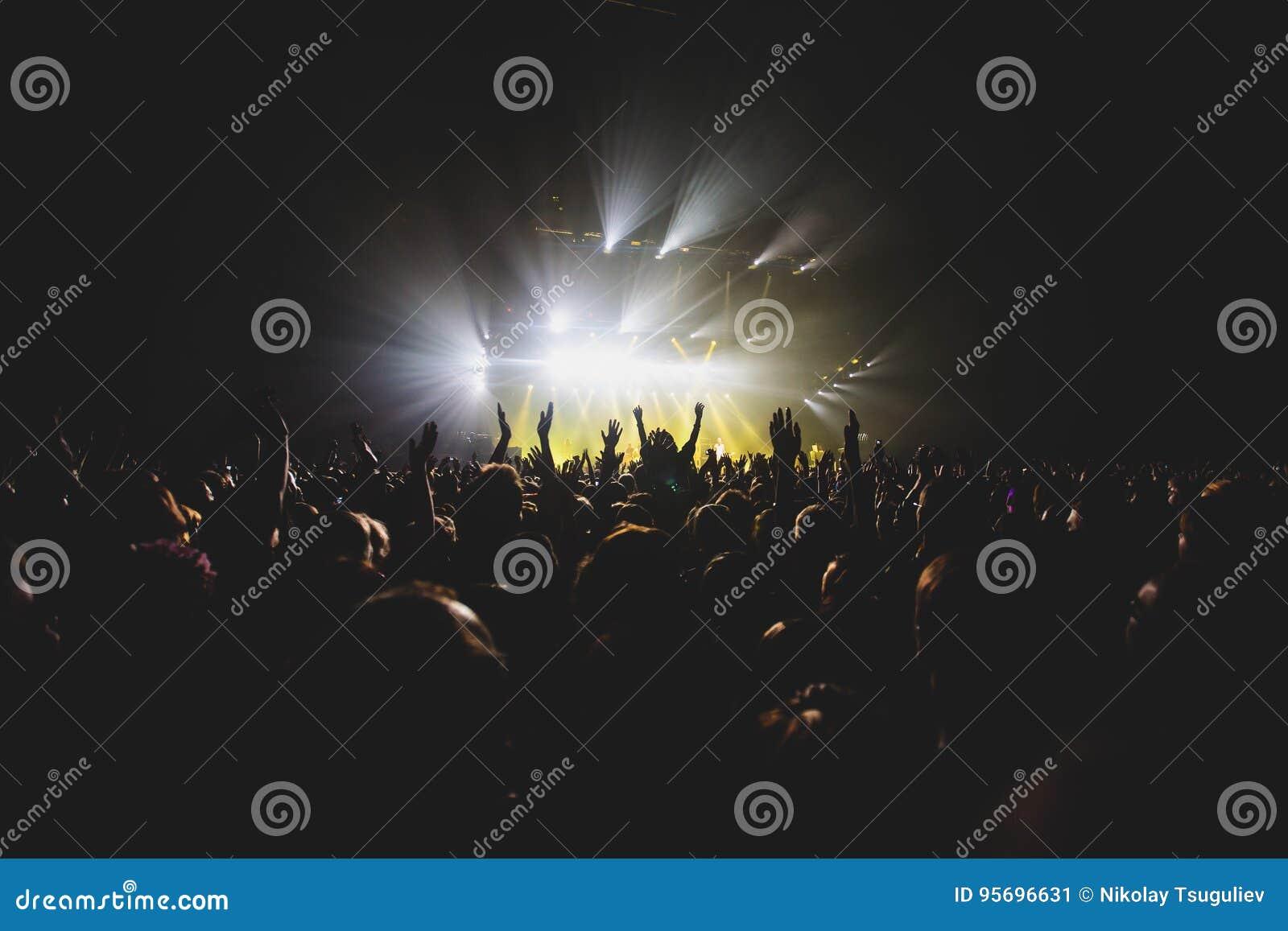 Взгляд выставки рок-концерта в большом концертном зале, с толпой и этапом освещает, толпить концертный зал с сценой освещает, pe