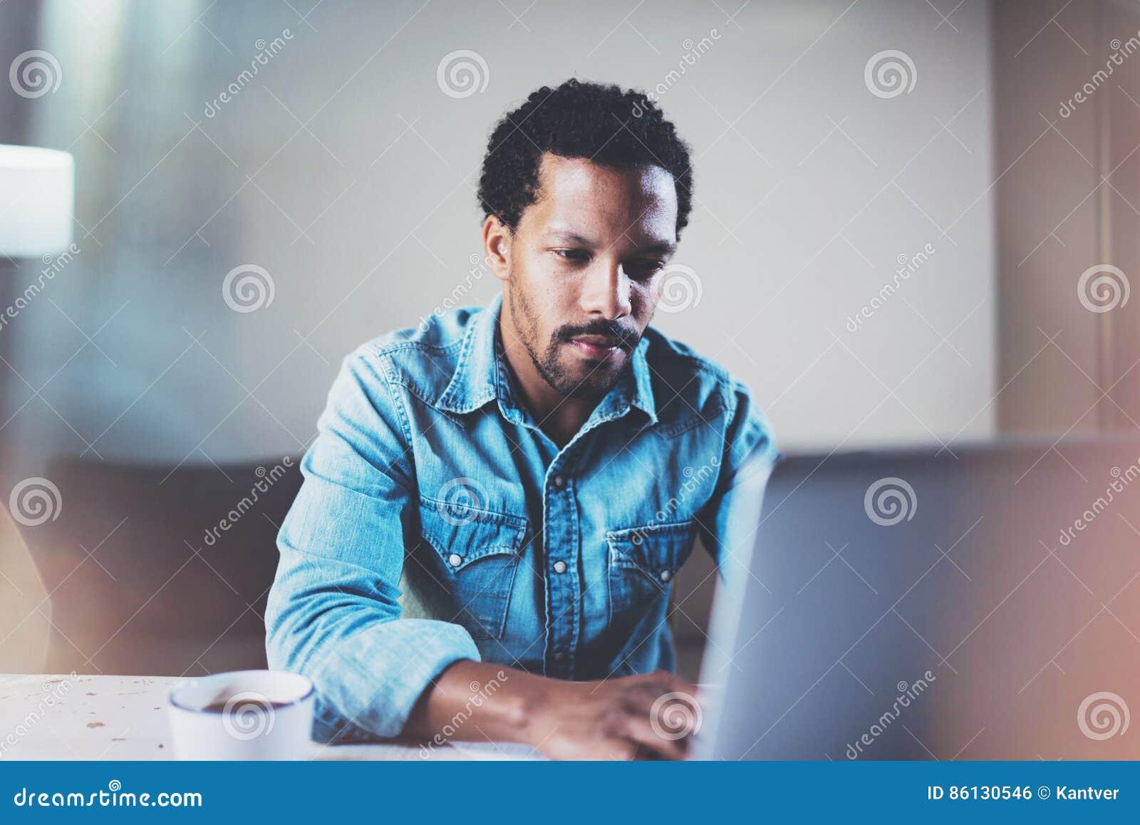Взгляд крупного плана задумчивого бородатого африканского человека используя компьтер-книжку на coworking космосе на деревянном с