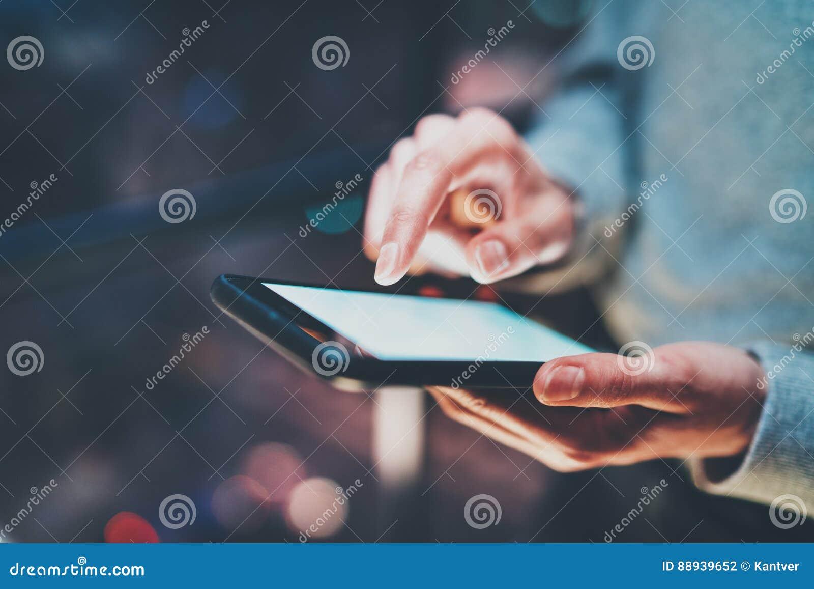 Взгляд крупного плана smartphone держа в женских руках Экран девушки касающий белый пустой Горизонтальная, запачканная предпосылк