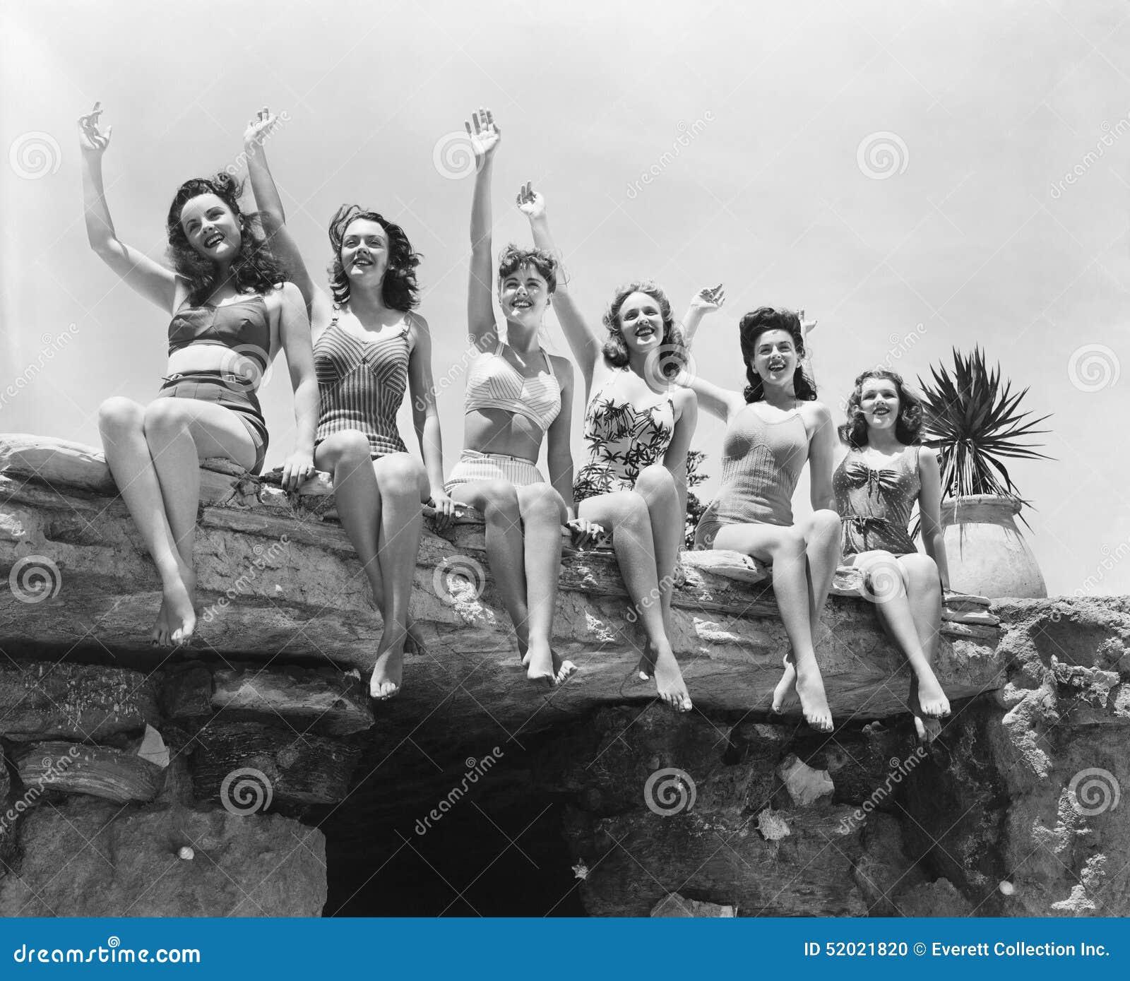 Взгляд низкого угла группы в составе женщины сидя на каменной структуре и развевая их руки (все показанные люди нет более длинног