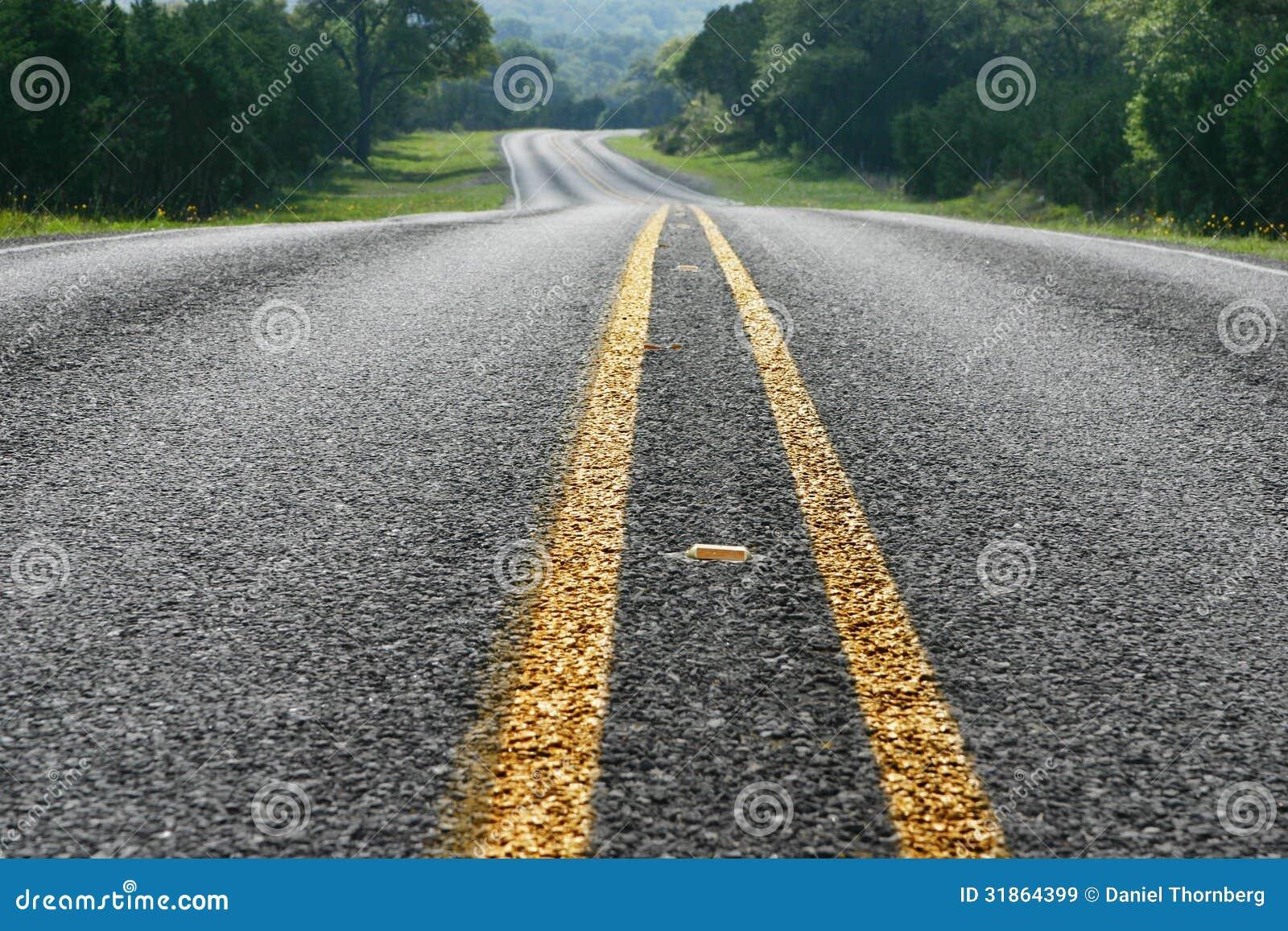 Взгляд низкого угла изгибать дорогу в стране холма Техаса